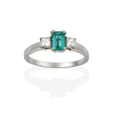 Lot 2081 - An 18 Carat White Gold Emerald and Diamond Three Stone Ring, the emerald-cut emerald flanked by...