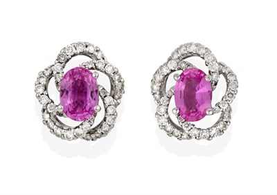 Lot 2082 - A Pair of 18 Carat White Gold Pink Sapphire and Diamond Cluster Earrings, the oval cut pink...