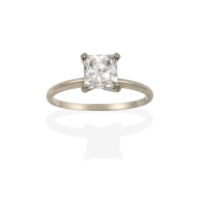 Lot 2083 - A Diamond Solitaire Ring, the princess cut diamond in a white four claw setting, to a tapered...