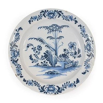 Lot 23 - An English Delft Charger, probably Liverpool, circa 1750, painted in blue with bamboo, peony...