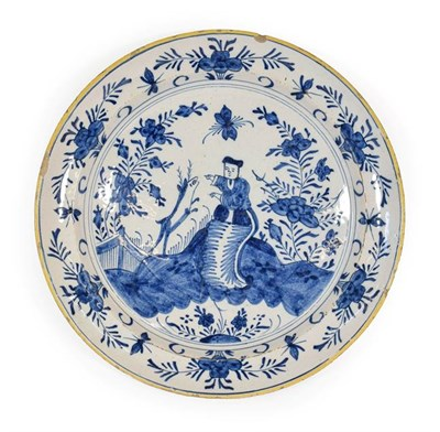 Lot 64 - A Delft Dish, circa 1750, painted in blue with a Chinese figure and a deer in a fenced garden...