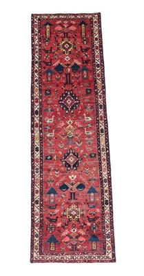Lot 353 - Narrow Heriz Runner North West Iran, circa 1940 The soft tomato red field with a one way design...