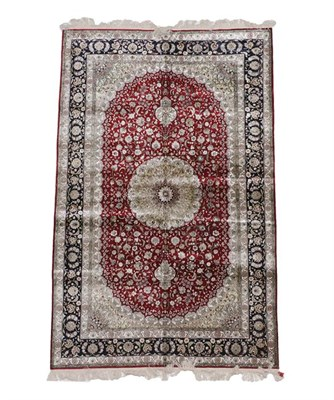 Lot 386 - Modern Chinese Silk Rug The claret field of scrolling vines around a flowerhead medallion framed by