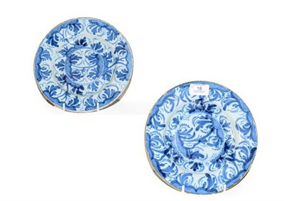 Lot 18 - A pair of 18th century Delft blue and white plates painted with stylized trees under orange...