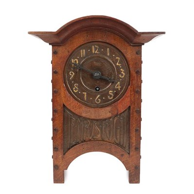 Lot 1040 - An Arts & Crafts Oak and Copper Mantel Clock, domed top, oak rivets, the hammered dial with...