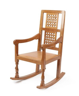 Lot 1064 - Workshop of Robert Mouseman Thompson (Kilburn): An English Oak Rocking Chair, with two lattice...