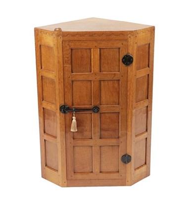Lot 1065 - Workshop of Robert Mouseman Thompson (Kilburn): An English Oak Hanging Corner Cupboard, with...
