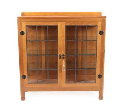 Lot 1067 - Workshop of Robert Mouseman Thompson (Kilburn): An English Oak Display Cupboard, with raised...