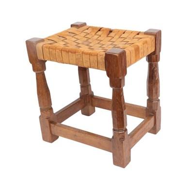Lot 1093 - Workshop of Robert Mouseman Thompson (Kilburn): An English Oak Stool, leather strap top, on...