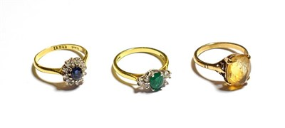 Lot 64 - An 18 carat gold emerald and diamond ring, finger size M, a sapphire and diamond cluster ring,...