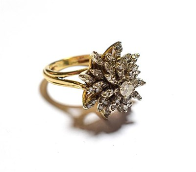 Lot 76 - A diamond cluster ring, the central raised round brilliant cut diamond within a radiating border of