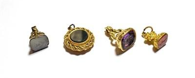 Lot 90 - A gilt metal fob seal set with carnelian; a gilt metal fob seal set with purple glass, another gilt