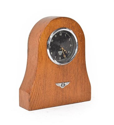Lot 8 - A 1930's Smith's Car Clock, mounted in an oak case with Bentley winged badge emblem, 20cm high