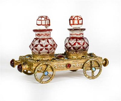Lot 13 - A Gilt-Metal, Gem-Set and Enameled Bottle-Stand, in the form of a flatbed rail carriage, set...