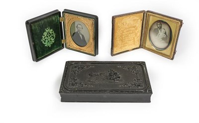 Lot 86 - A daguerreotype of a gentleman holding a baby, in fitted leather covered case, stamped...