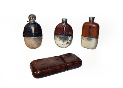 Lot 59 - A crocodile skin cigar pouch together with three silver plated and crocodile skin mounted hip...