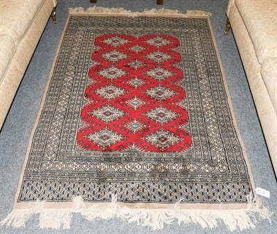 Lot 1012 - A Kashmir Bukhara rug, the crimson field with two rows of güls enclosed by multiple borders, 179cm