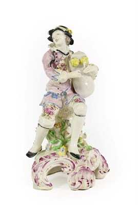 Lot 35 - A Bow Porcelain Figure of a Bagpiper, circa 1765, seated on a rocky outcrop on a scroll moulded...