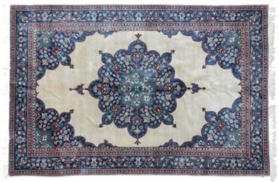 Lot 300 - Indian Carpet, 2nd half 20th century The plain cream field with indigo flower head medallion framed