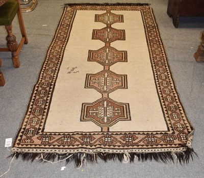 Lot 1004 - Gabbeh rug, the ivory field with linked medallions, framed by border of geometric motifs, 288cm...