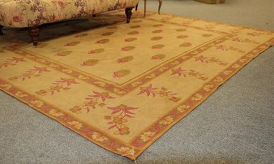 Lot 1008 - A machine made rug of Aubosson design, the pale camel ground of plants enclosed by borders of...