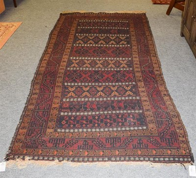 Lot 1010 - Baluch Soumakh rug, the field with indigo and burgundy bands of tribal devices enclosed by...