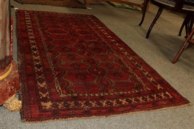 Lot 1011 - Baluch Rug, the crimson field with three crenellated panels comprising hooked guls enclosed by...