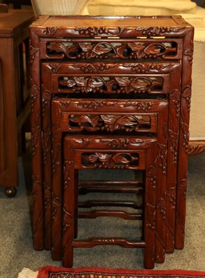 Lot 1093 - A 20th century Chinese hardwood nest of four tables carved with leaves and berries, 47cm by 34cm by