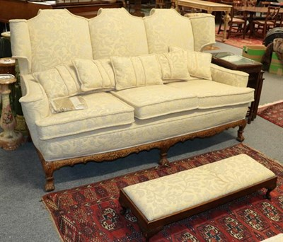 Lot 1094 - A Georgian style three-piece suite comprising a three seater sofa and pair of wing back...