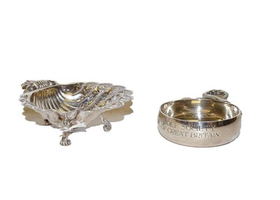 Lot 44 - An Elizabeth II silver wine taster and a shell shaped dish (2)