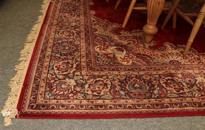 Lot 1076 - Machine made carpet of oriental design, the blood red field with central medallion framed by...