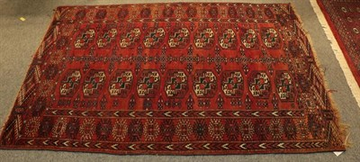 Lot 1077 - Paskistani Bukhara rug, the deep terracotta field with four columns of guls enclosed by stellar...