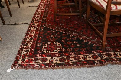 Lot 1080 - Kashgai Carpet, the brick red field with three linked stepped medallions framed by spandrels...