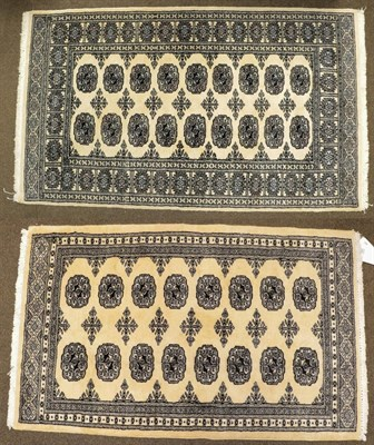 Lot 1091 - A Kashmiri 'Bukhara' Rug, the ivory field with columns of guls enclosed by narrow borders,...