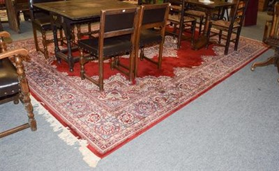 Lot 1083 - Machine made carpet of oriental design, the blood red field with central medallion, framed by...