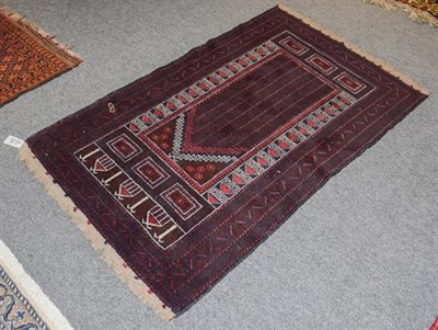 Lot 1086 - An Afghan Baluch rug the field with columns of barber poles beneath the Mihrab enclosed by...