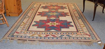 Lot 1090 - Kozak Anatolian Carpet, the ivory field with three Lesghi guls enclosed by leaf and calyx...