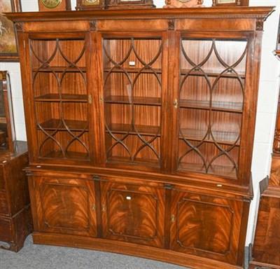 Lot 1100 - A reproduction concave mahogany bookcase, comprising three astragal glazed doors, above three...
