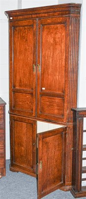 Lot 1103 - A large Georgian oak standing corner cupboard, with panelled doors and fluted pilasters, 114cm...