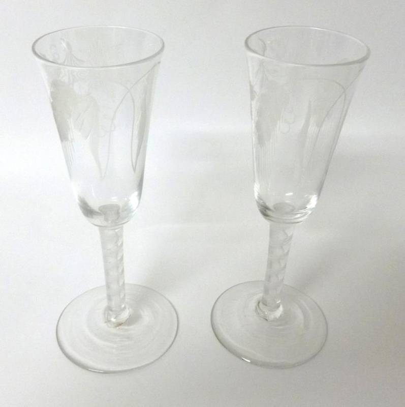 Lot 10 - A Pair of Ale Flutes, circa 1760, the rounded funnel bowls engraved with hops and barley on a...