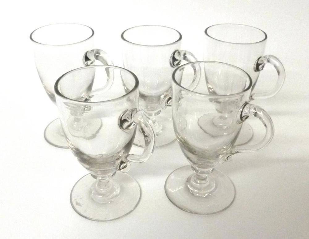 Lot 28 - A Set of Five Custard Cups, circa 1800, the slender ovoid bowls with trailed handles on waisted...